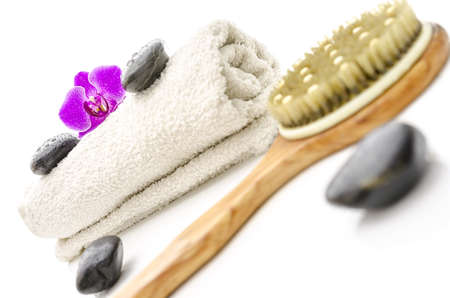 Wellness setting with massage stones, violet orchid flower, brush and towel  photo