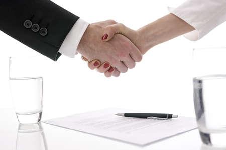 contratos: Hombre y mujer que sacuden las manos por encima de la mesa con contrato firmado
