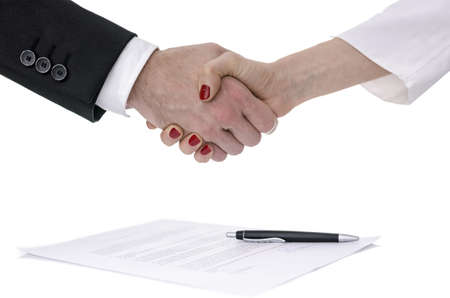 congratulating: Man and woman congratulating with handshake after signing a contract