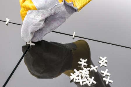 tegelwerk: Tegelzetters de hand tijdens het gebruik van spacer voor het installeren van een zwarte keramische tegels