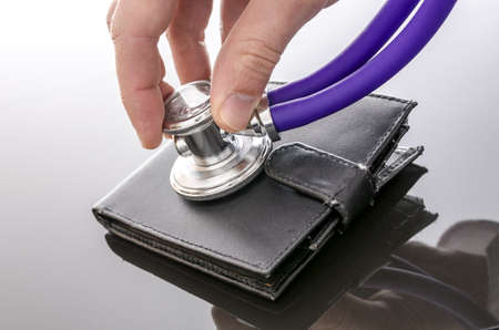 global crisis: Male hand checking an old wallet on a black table with a stethoscope  Stock Photo