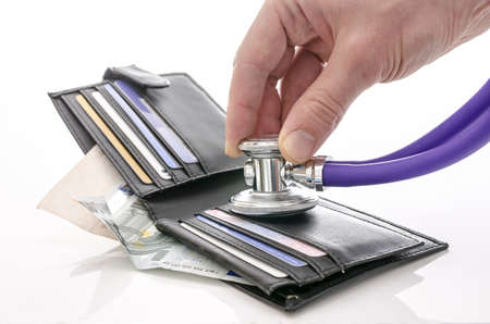 health insurance: Checking open wallet with stethoscope  Concept of financial crisis