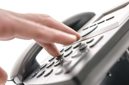 Detail of a hand pressing a button on a telephone keypad  With selective focus  photo