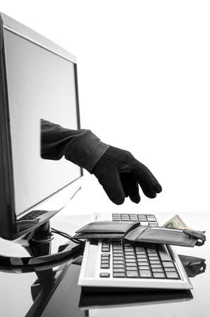 computer crime: Gloved hand of a thief stealing wallet through a computer screen  Concept of internet crime