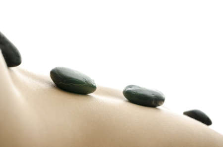 Side view of black massage stones on the back of a woman  With white background Stock Photo - 18266525