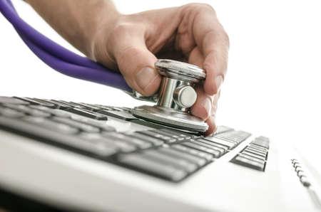 virus informatico: Prueba de un teclado de ordenador con estetoscopio Foto de archivo