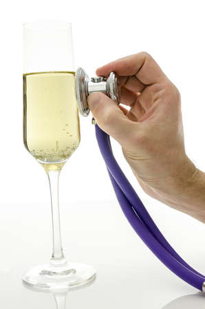 consequences: Male hand holding a stethoscope on a glass of wine Concept of consequences of drinking alcohol  Stock Photo
