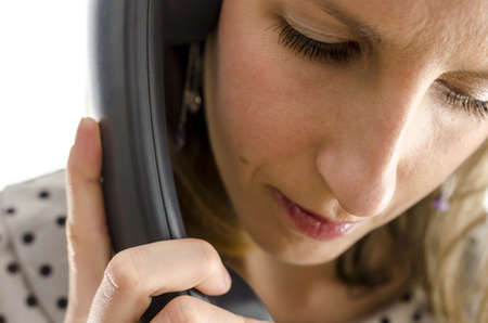 call center female: Portrait of a young woman on a phone looking down. Stock Photo