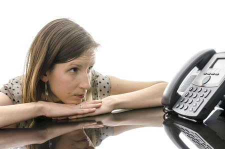 secretary phone: Woman waiting for a phone call while looking at telephone and leaning on a black table with reflection