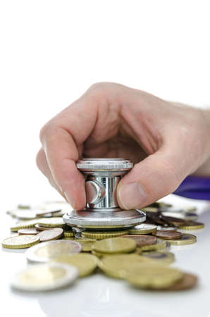 Male hand with stethoscope trying to heal bunch of coins  Concept of economic crisis recovery Stock Photo - 18539097