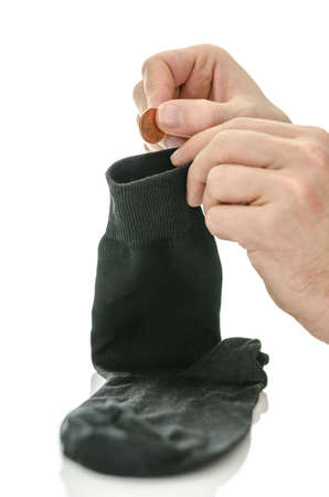 Man saving money in his black sock  Over white background Stock Photo - 18539104