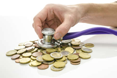 debt management: Solution to financial crisis concept  Male hand with stethoscope on Euro coins  Stock Photo