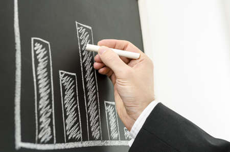 Side view of a businessmans hand drawing business graph with a chalk on a black board  photo