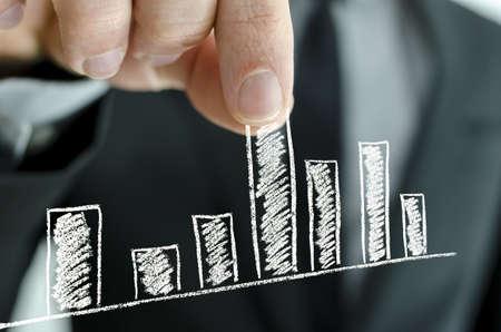 grafica de barras: Empresario tirando hacia arriba del gr�fico de columnas en una pantalla virtual