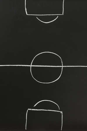 Top view of an empty soccer field sketched with white chalk on a black board