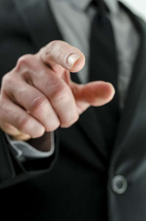 Cropped view of a hand with pointed finger. With businessman in suit in background. photo