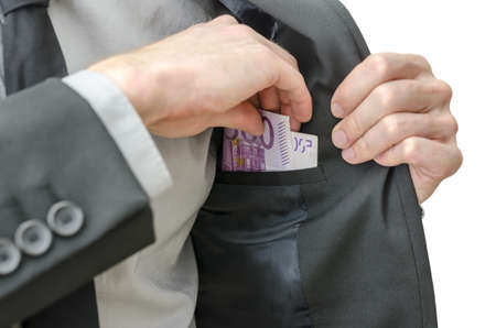 bribe: Closeup of a business man in suit putting banknotes in his jacket pocket. Stock Photo