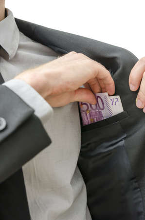 bribery: Man putting money in the inner pocket of his jacket  Concept of bribery and corruption  Stock Photo