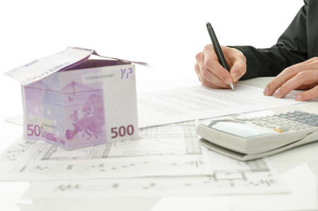 Signing contract of house sale with house made of 500 Euro money and  architectural building plan on a white table  photo