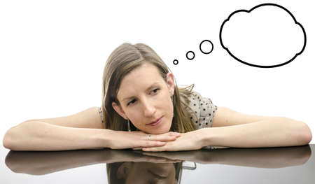 Thoughtful young brunette leaning with chin on her hand with empty thought bubbles  On a black table Stock Photo - 18811946