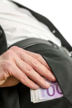 bolsa dinero: Vista inferior del hombre de negocios joven que pone el dinero en el bolsillo del pantalón Foto de archivo