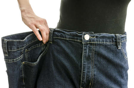Closeup of a slim woman waist in oversized pants after losing a lot of weight  Over white background  photo