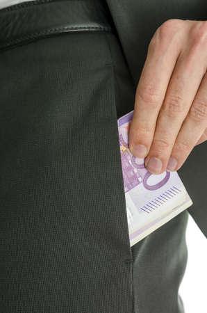 bolsa dinero: Detalle de una mano masculina que poner 500 billetes de euro en bolsillo de los pantalones de un traje Foto de archivo