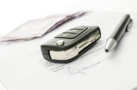 car loans: Black car key and money on a signed contract of car sale   Focus on a key  Stock Photo