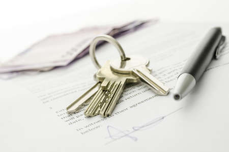 new contract: Keys of a new house on a signed contract of house sale with money in background  Concept of closed deal  Stock Photo