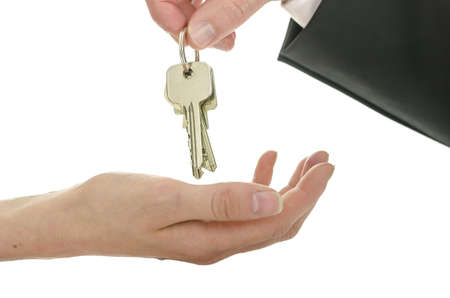 key handover: Man handing house keys over to a new owner  Isolated over white background  Stock Photo