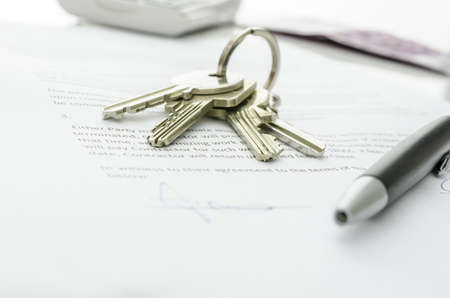 purchased: House keys and money on a signed contract of house sale   Focus on keys  Stock Photo
