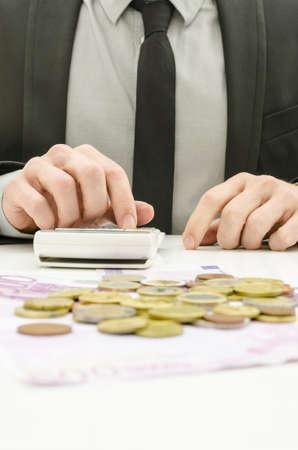 administracion de empresas: Cierre de contador masculino en traje cálculo de los gastos con el dinero euro sobre la mesa