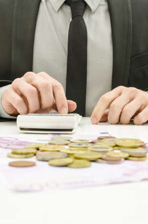 calculation: Close up of male accountant in suit calculating expenses  With Euro money on his desk