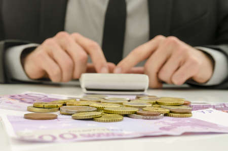 billing: Front view of financial adviser working  With Euro banknotes and coins on his desk  Focus on money