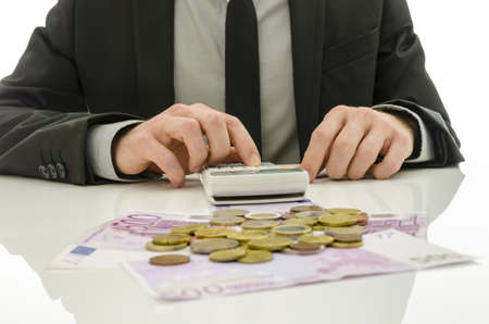 expenses: Detail of businessman working on calculator counting expenses  With Euro coins and banknotes on his white table  Stock Photo
