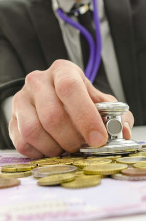 Male hand holding stethoscope over Euro coins and banknotes. Stock Photo - 18964555