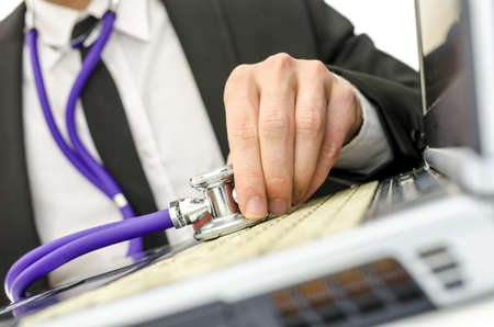 Close up of repairman holding stethoscope on his old laptop keyboard   photo