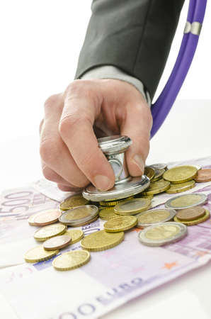 Detail of banker hand holding stethoscope over Euro coins and banknotes. Over white background. Stock Photo - 19249580