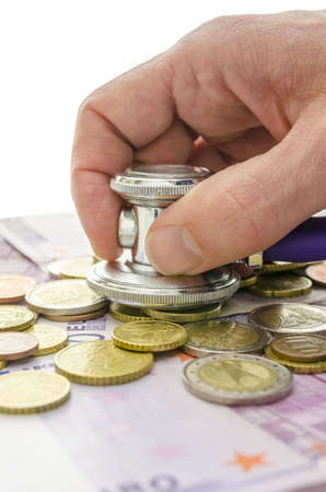 Detail of male hand checking Euro banknotes and coins with stethoscope. Solution to financial crisis concept. Stock Photo - 19249583