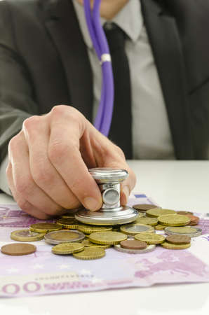 Closeup of financial advisor checking European union currency with stethoscope. Stock Photo - 19249581