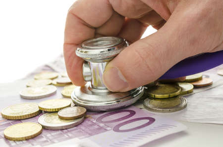 Male hand holding stethoscope on European currency  Concept of financial crisis solution  Stock Photo - 19249584