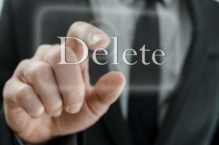 Homme d'affaires touchant le bouton Delete sur un écran virtuel