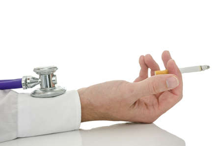 Stethoscope on a hand holding a cigarette  Isolated over white background  photo