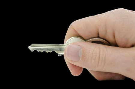 Male hand holding house key  Isolated over black background  photo