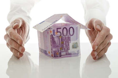 Male hands giving energy to money house  Concept of real estate crisis solution  Stock Photo - 19474043