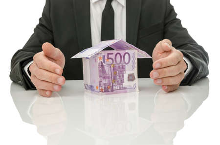 Male hands around house made of Euro money  Concept of real estate and insurance crisis solution  photo