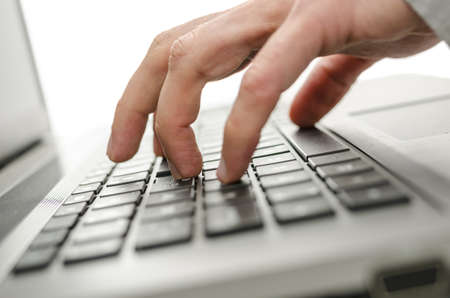 Male hand typing on laptop keyboard  photo
