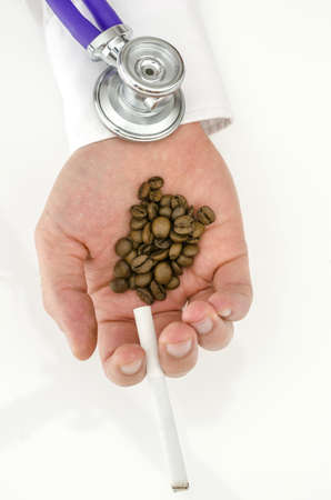 Top view of stethoscope on smoke and coffee addict hand  photo