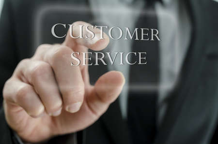 Close up of business man pointing at Customer service icon on a virtual screen  photo