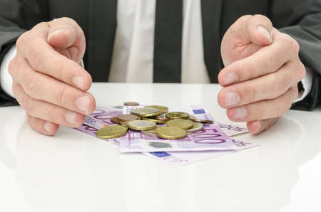 Businessman holding hand around Euro money as if giving it power and energy  Concept of help and solution for recession Stock Photo - 19474270